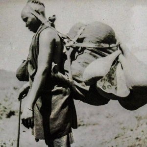 A gîkûyû woman with a load suspended using a head strap.‬